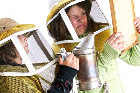 beekeeper: Closeup of an eight year old boy and a twelve year old girl in protective beekeeper hats carefully using a smoker to calm bees in a honey comb  These children are learning beekeeping skills that will protect the environment and encourage locally produced  Stock Photo