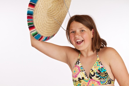 Cropped image of a laughing 12 year old girl happily waving her straw Mexican hat in the air  Isolated on white background with room for copy