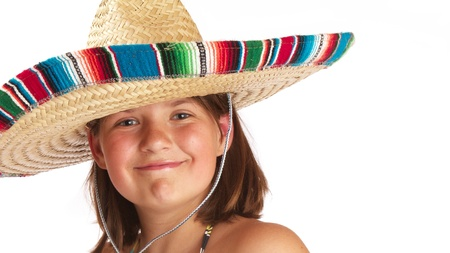 Closeup of smiling young girl wearing colorful straw Mexican sun hat, isolated on white background with copy spacwe  photo
