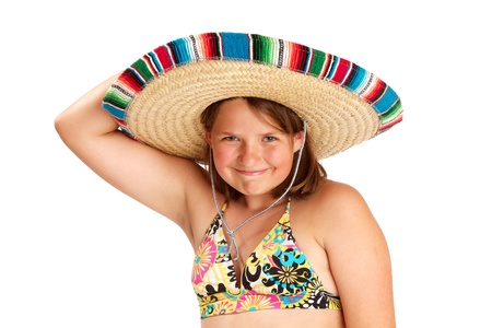 cropped image: Cropped image of a smiling 12 year old girl, one raised arm holding her straw Mexican hat to her head  She wears a tropical print halter top  Isolated on white background with copy space