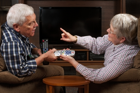 Senior married couple sits in front of television in arguing over who gets to have the remote control. Horizontal format with copy space. Stock Photo