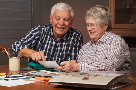 foto: Happy senior echtpaar het delen van herinneringen tijdens het werken aan familie foto album samen. Horizontale formaat.
