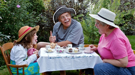 clowning: Grandparents and 6 year old granddaughter sit at a small table in a garden, having a tea party and making funny faces at each other. Straw hats, china tea cups, cupcakes, and embroidered tablecloth are accessories. Horizontal format.