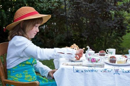 muneca vintage: Peque�a ni�a 6 a�os est� vestido con su mejor traje, sentado en una peque�a mesa en un jard�n encantador. Ella tiene una antig�edad de t� de porcelana conjunto del partido y magdalenas de lujo, con un mantel bordado. Foto de archivo