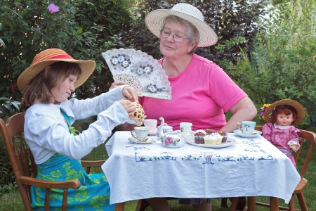 for tea: A charming spring garden is a perfect setting for a loving grandmother and her 6 year old granddaughter to have a tea party, accompanied by a vintage doll. Accessories include a lace fan, pretty straw hats, bright pastel dresses, delicate antique china te