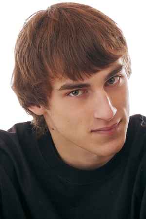 Head and shoulders portrait of smiling teenage boy, brown hair, gray eyes, gray hooded sweater, direct gaze. Dark background, vertical format.