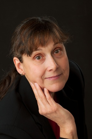 lowkey: MIddle-aged woman with kind, calm expression and large brown eyes rests hand on cheek and looks up. Low-key image isolated on black background with copy space. Stock Photo