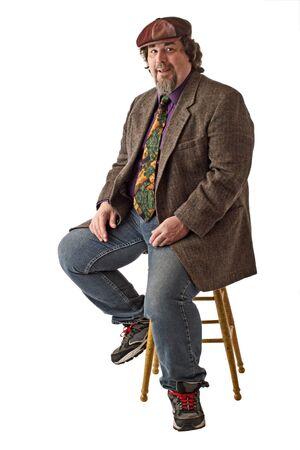 Hombre con construcción grande se sienta en el taburete, vestido de manera informal en tweed gorra, chaqueta y pantalones vaqueros. Él sonríe y se inclina hacia adelante con las manos en las rodillas. Vertical, aisladas sobre fondo blanco, copia espacio.