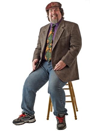 large build: L'uomo con la costruzione di grandi dimensioni si siede sullo sgabello, vestiti casual in tweed cap, giacca e jeans. Si appoggia indietro e ride. Verticale, isolato su sfondo bianco, copia spazio.
