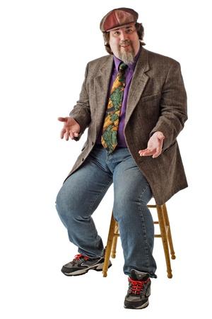 large build: L'uomo con la costruzione di grandi dimensioni si siede sullo sgabello, vestiti casual in tweed cap, giacca e jeans. Alza le spalle con i palmi in su. Verticale, isolato su sfondo bianco, copia spazio.