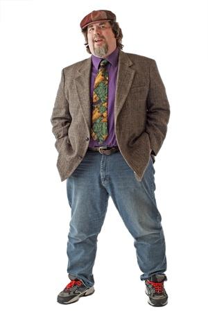 Velký muž v tvídové čepici a bundu úsměvů a stojí s rukama v pockets.Isolated na bílém pozadí, vertikální, copy space. Reklamní fotografie