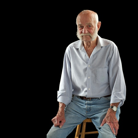 Elderly man listens, looks thoughtful, raises eyebrows, sits facing forward and rests hands on thighs. He is bald with white mutton chop whiskers, wears jeans and open-collared shirt. Square composition, isolated on black, copy space. photo