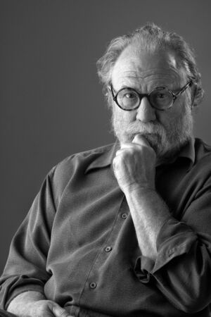 Senior man with white beard and round glasses thoughtfully rests hand on chin  Low key monochrome, vertical layout with copy space