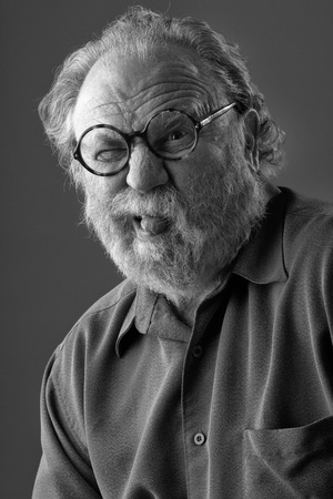 Senior man with white beard and round glasses sticks out tongue  Monochrome, vertical layout with copy space  photo