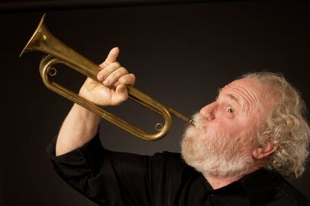 Side view of a bearded senior musician blowing a bugle, held with an expressively raised little finger  Black background, horizontal format and copy space