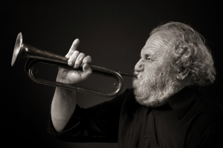 Bearded old man blowing a bugle with gusto