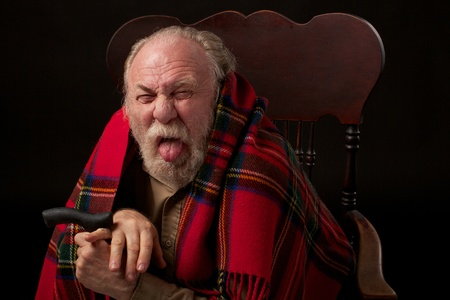 Old man with gray beard with bright red plaid shawl sits hunched over his cane and sticks out his tongue  Head and shoulders portrait in a low key horizontal image