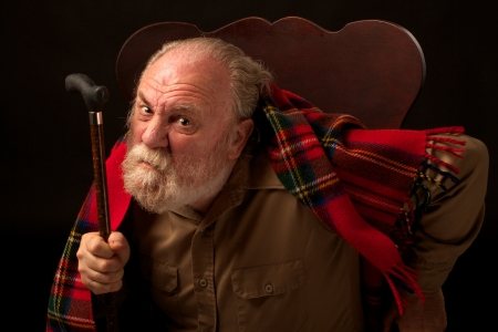 Leaning forward in his chair, an old man with gray beard looks directly at the camera, frowns, raises his cane and shakes it  He has a dark tan shirt and red plaid wool shawl  Horizontal composition with spot lighting and a black background  Stock Photo