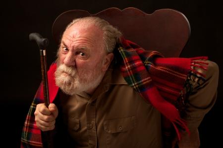 Naklonil se dopředu na židli, starý muž s šedivým plnovousem se dívá přímo do kamery, zamračí, zvedne hůl a chvění, že on má tmavě tan košili a červené kostkované vlna šátek horizontální kompozice s bodovým osvětlením a na černém pozadí Reklamní fotografie