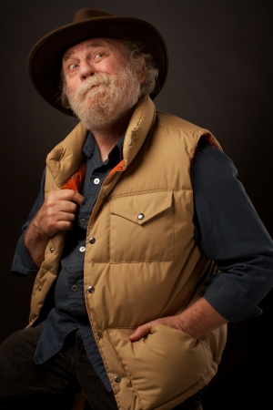Senior man looks up with amused expression  He has a grey beard, brimmed felt hat, and his hand is in the pocket of his puffy down vest  Casual three-quarter pose  Vertical, dark background, copy space