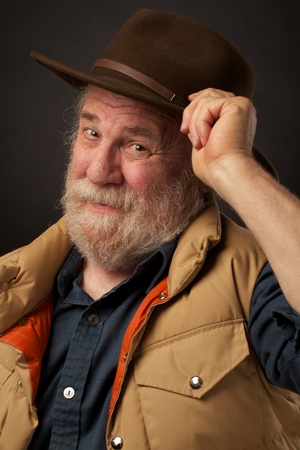 A friendly bearded senior man smiles and tips his brown slouch hat with one hand  He wears a sleeveless tan down vest and denim shirt  Dark background, horizontal composition, copy space  Stock Photo - 14570264