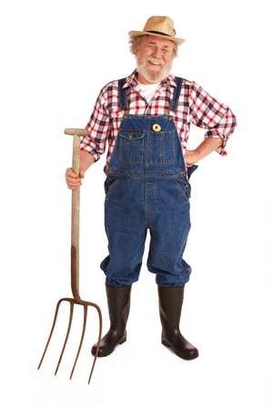 Classic s úsměvem senior farmář s slaměný klobouk, kostkované košili, bryndáček, drží seno vidlice vertikální rozložení, izolovaných na bílém podkladovými s kopií vesmíru
