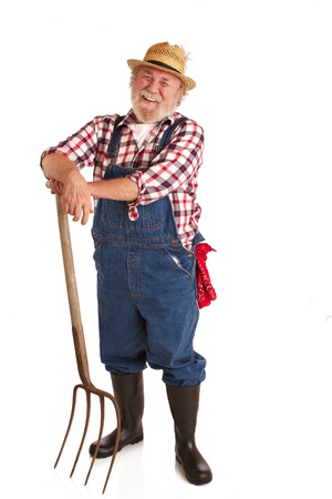 Classic smiling senior farmer with straw hat, plaid shirt, bib overalls, and hay fork  Vertical layout, isolated on white backgound with copy space