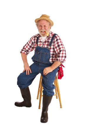 Classic smiling senior farmer with straw hat, plaid shirt, bib overalls, corn cob pipe  He sits on a stool   Vertical layout, isolated on white background with copy space