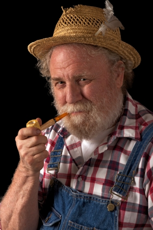Classic smiling senior farmer with straw hat, plaid shirt, bib overalls, and corn cob pipe  Vertical layout, isolated on black backgound with copy space