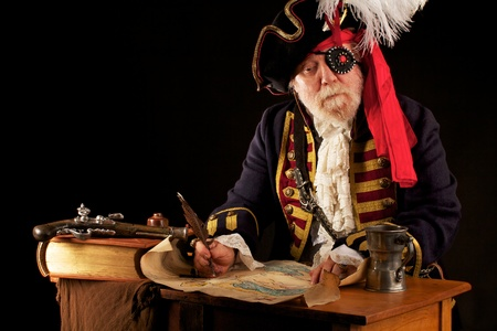 Colorful gray bearded pirate captain sits at his desk, drawing a treasure map with a feather quill pen  His musket, a thick leather bound book, and pewter mug are beside him  Dramatic lighting, black background, a horizontal layout, and space for copy  photo