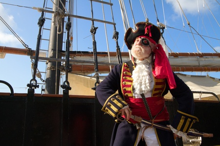 Proud old pirate in colorful traditional costume stands on board ship and draws his sword  Schooner rigging and blue sky in background, horizontal layout with copy space