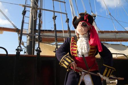 Trotse oude piraat in kleurrijke traditionele klederdracht staat aan boord van het schip en trekt zijn zwaard Schooner tuigage en de blauwe hemel op de achtergrond, horizontale lay-out met een kopie ruimte