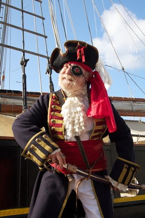 Happy smiling old pirate in colorful traditional costume stands on board ship and draws his sword  Schooner rigging and blue sky in background, vertical layout