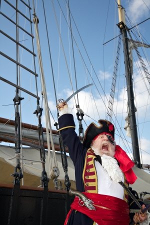 Pirate captain in colorful traditional costume stands on board ship, shouts, and waves his sword  Sailing ship rigging and blue sky in background, vertical layout