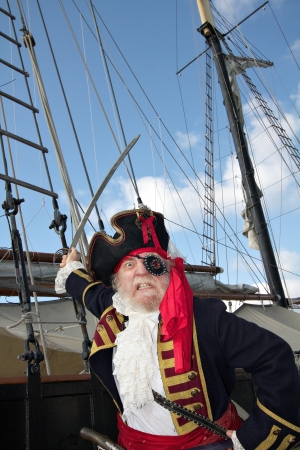 Angry bearded pirate captain in colorful traditional costume stands on board ship and waves his sword  Schooner rigging and blue sky in background, vertical layout