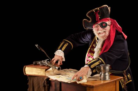 Gleeful old pirate captain sits at his table with still life of log book, quill pen, musket, pewter mug, and tattered weather beaten treasure map  He is wearing an authentic looking 19th century pirate costume with jewelled eye patch, braided topcoat, lac