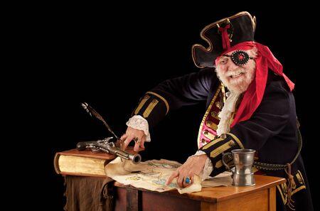 Vrolijke oude piraat kapitein zit aan zijn tafel met stilleven van logboek, ganzenveer, musket, tinnen mok, en gescheurde weer geslagen schatkaart Hij draagt een authentiek uitziende 19e-eeuwse piraat kostuum met juwelen bezette ooglapje, gevlochten toplaag, lac