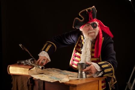 Barevně kostýmech šedá vousatý kapitán pirátů sedí s mapou pokladů a cínové hrnek, kterému čelí, přední a dívá přes rameno Dramatic boční osvětlení efekt Černé pozadí a horizontální uspořádání s prostorem pro kopírování
