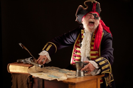 Colorful happy old pirate captain in 18th century style costume, seated with a torn treasure map spread out on wooden desk, illuminated by a ray of intense light  He holds a pewter mug and is laughing uproariously, head thrown back  Dramatic side lighting photo