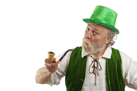 Classic wrinkled old Irish leprechaun with white beard, top hat, and green velvet vest  He holds up curved calabash pipe, raises his eyebrows, purses his lips and tilts his head  Isolated on white, horizontal layout with copy space