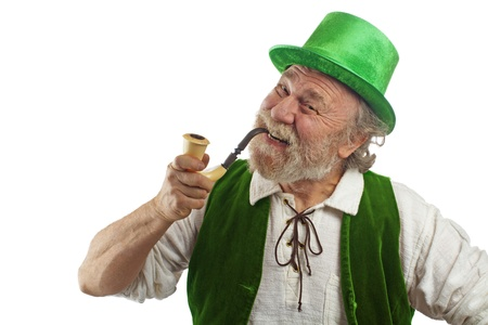 Classic happy Irish leprechaun with white beard, top hat, green velvet vest, and curved pipe in mouth  He rraises his eyebrows, smiles and tilts his head  Isolated on white, horizontal layout with copy space  Stock Photo