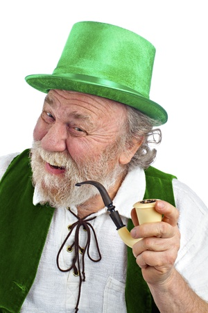 Classic happy Irish leprechaun with white beard, top hat, green velvet vest, and curved pipe in hand  He raises his eyebrows, smiles and tilts his head  Isolated on white, vertical layout with copy space  photo