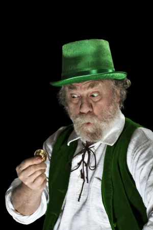 Classic Irish leprechaun with white beard, top hat, green velvet vest, looking amazed at a gold coin  He raises his eyebrows, purses lips and widens his eyes  Up lighting, isolated on black, vertical layout with copy space