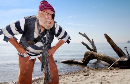Ragged schipbreukeling piraat op het strand ontbloot zijn tanden en leunt naar voren, de verdediging van schatkist in de buurt