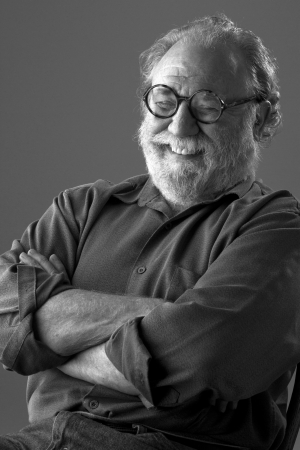 Senior man with white beard and round glasses leans back and laughs  Low key monochrome, vertical layout with copy space  photo