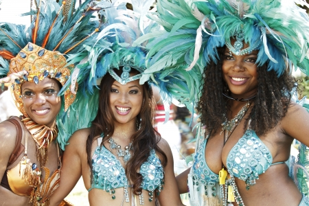 Three beautiful smiling young women dressed in glittering feathered Caribbean festival costumes