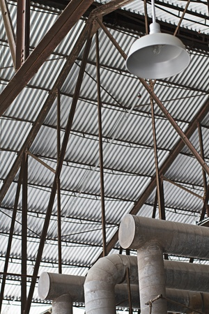 girders: Looking up at high steel girders supporting corrugated metal factory roof and hanging light fixture, with duct pipes