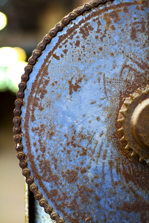 rusty chain: Curved edge closeup of old rusty blue machine gear with chain  Vertical, blur background, copy space   Stock Photo