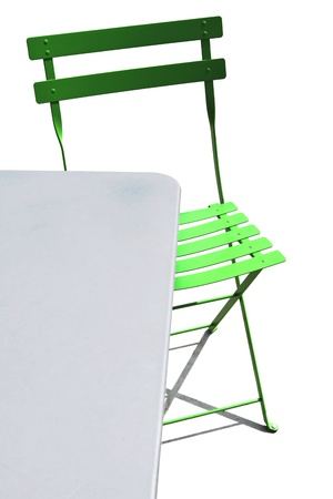 Outdoor metal folding patio table and lime green slatted chair make abstract design photo