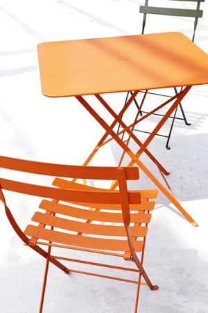 Colorful metal patio table and slatted chair with their shadows make abstract design